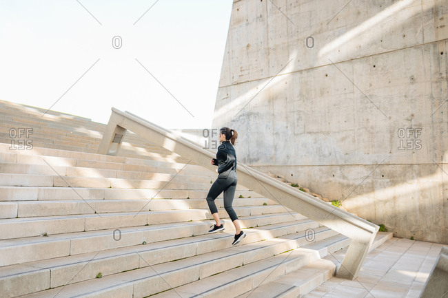 Young athlete running, warming up, climbing stairs