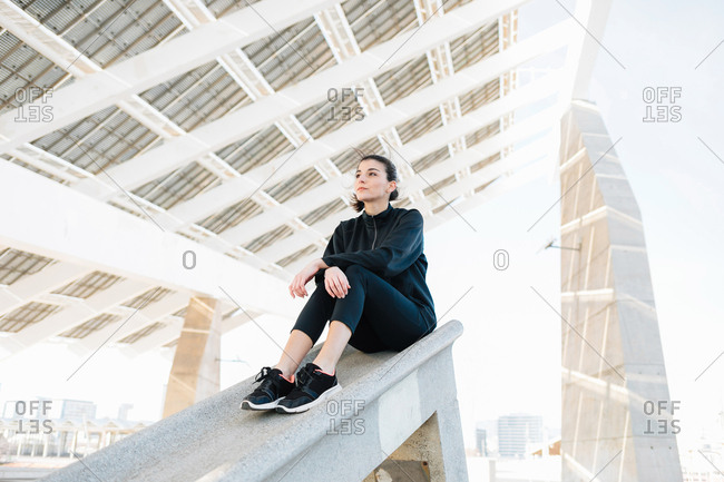 Young athlete sitting, looking into distance