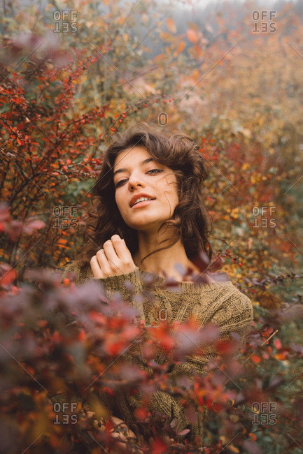 Portrait of a beautiful woman between red leaves