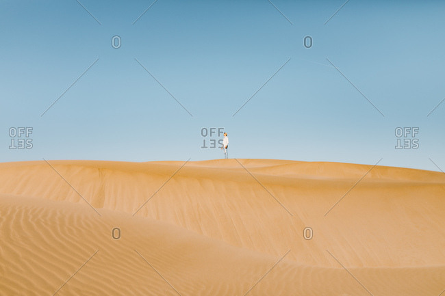 Man standing on a dune of a desert, looking up