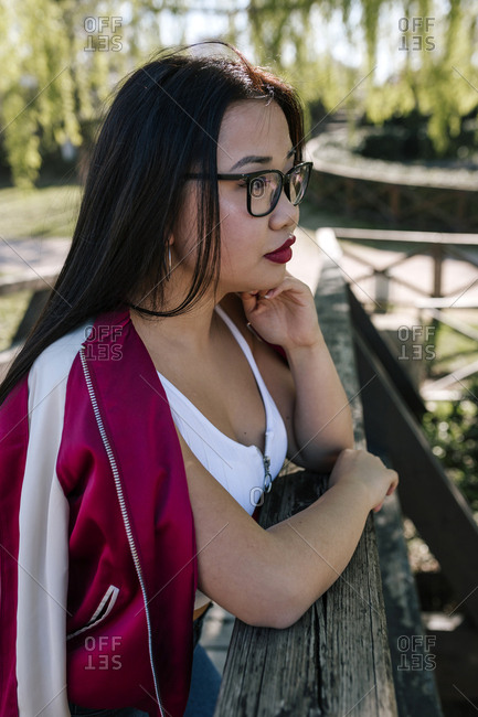 Beautiful Chinese woman with glasses of pasta in a nice park.