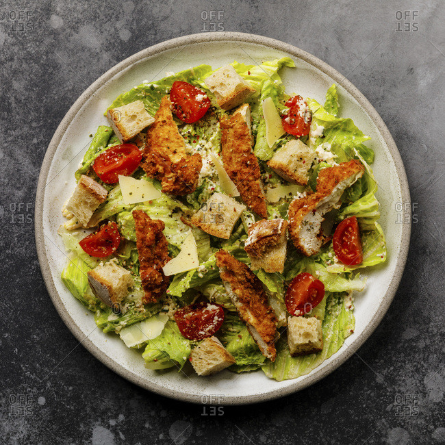Caesar salad with Chicken breast meat on gray background