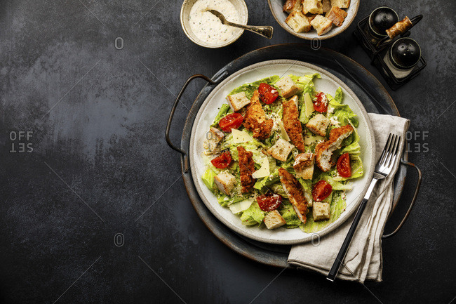 Caesar salad with Chicken breast meat on metal tray on dark background copy space