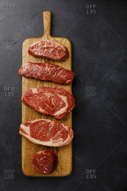 Variety of Raw Black Angus Prime meat steaks Top Blade, Denver, Rib Eye, Striploin, Tenderloin fillet Mignon on wooden board on dark background