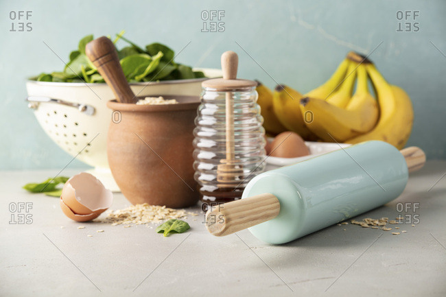 Ingredients for cooking spinach or banana pancakes or baking spinach or banana muffins- oats,  bananas, rolling pin, eggs, spinach, honey
