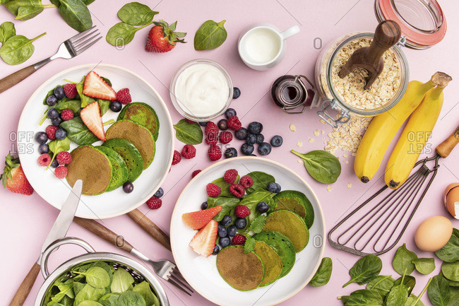 Spinach pancakes with fruits and vegetables on pink background, flat lay