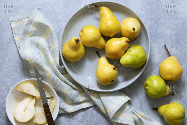 Whole pears with sliced pear in a dish.