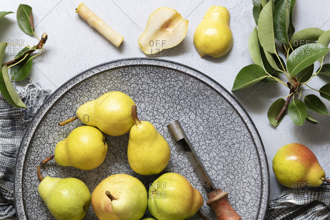 A cored and halved ripe pear with whole pears on a plate.