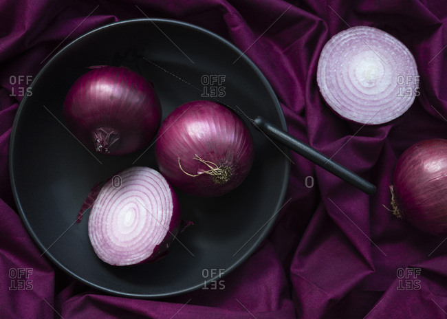 A whole red onion and a cut red onion in a bowl.