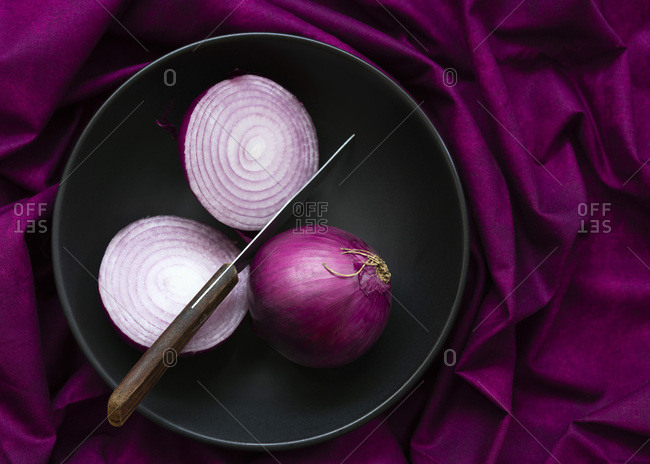 A red onion cut in half with a whole red onion.