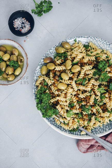 Lentil pasta garnished with parsley and green olives photographed on a grey background.