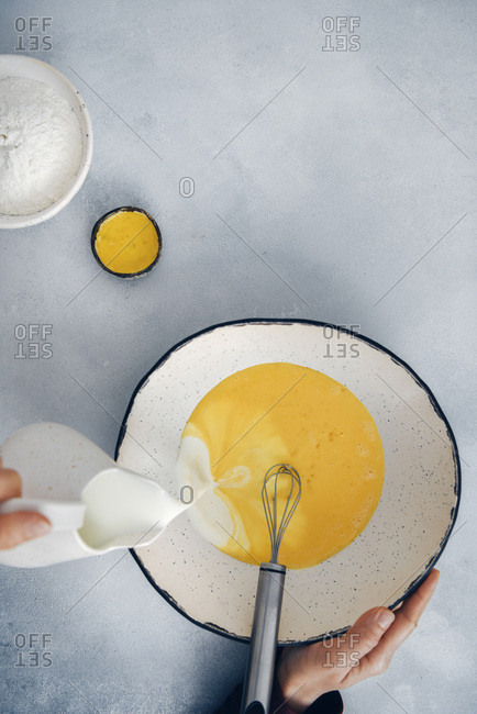 Woman pouring milk into beaten eggs in a large ceramic mixing bowl.