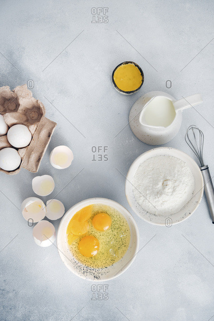 Ingredients for gluten free crepes are photographed in white ceramic bowls on a grey background.