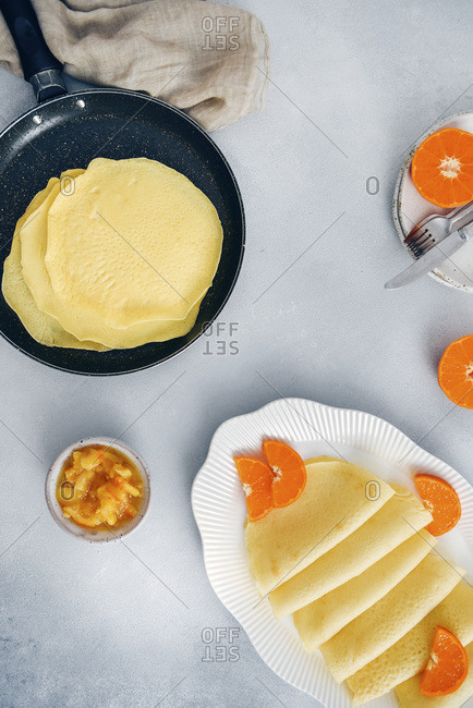 Gluten free crepes in a non stick pan and in a white oval plate garnished with orange slices, accompanied by orange jam.