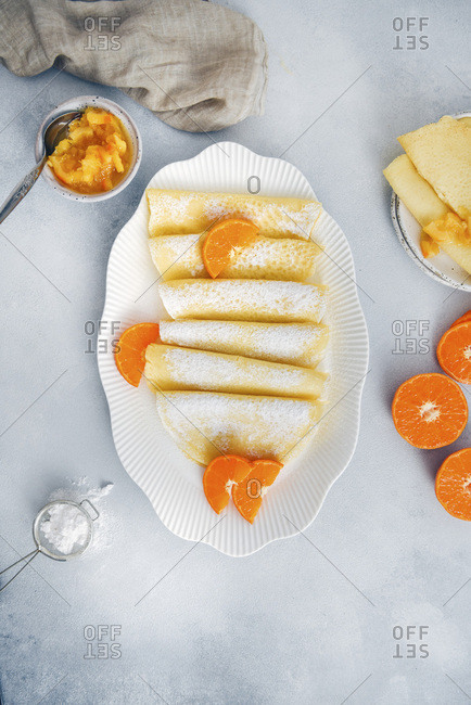 Gluten free crepes served in a white oval plate, garnished with orange slices and powdered sugar, accompanied by orange jam, mini strainer and halved oranges.
