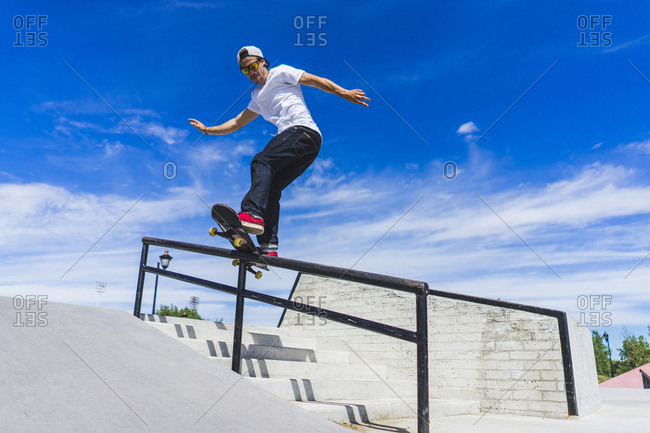 Male athlete on skateboard sliding down handrail, Montreal, Quebec, Canada