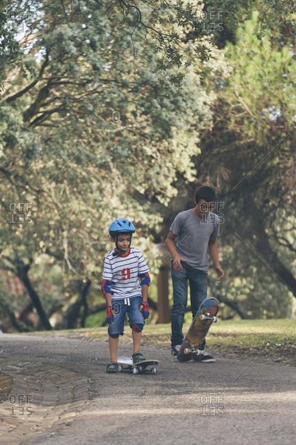 Brothers skateboarding in park