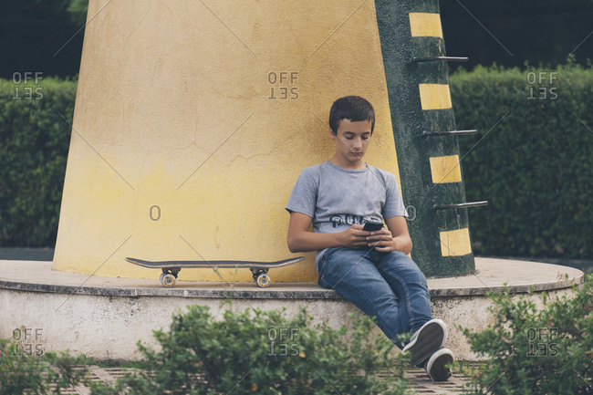 Teenage boy with skateboard using smart phone