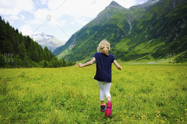 Carefree girl running in idyllic mountain valley, Innergschloess, Tyrol, Austria
