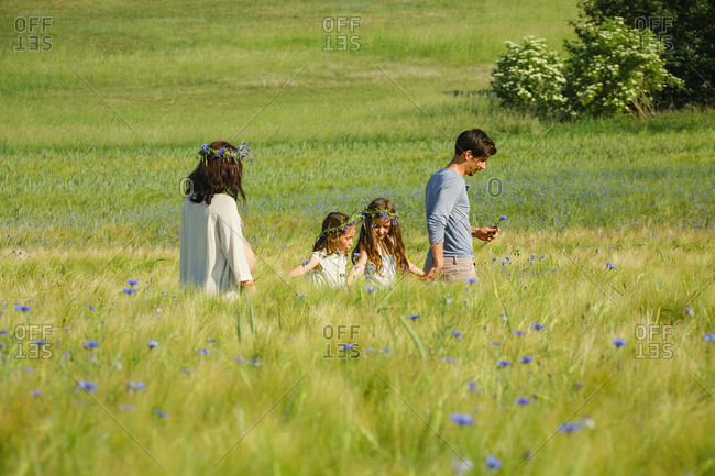 Family walking in sunny, idyllic rural green field with wildflowers