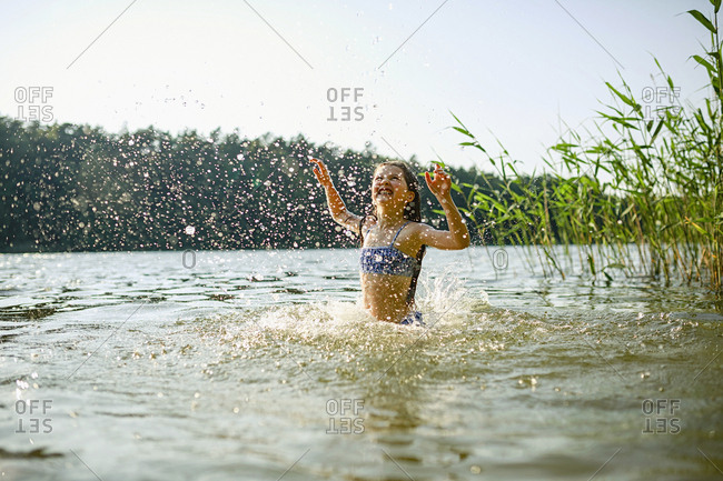 Playful girl splashing, swimming in sunny summer lake
