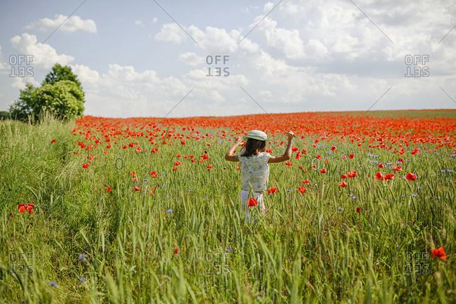 Girl running in sunny, idyllic rural red poppy field