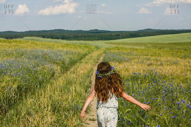 Girl running in sunny, rural idyllic green field with wildflowers