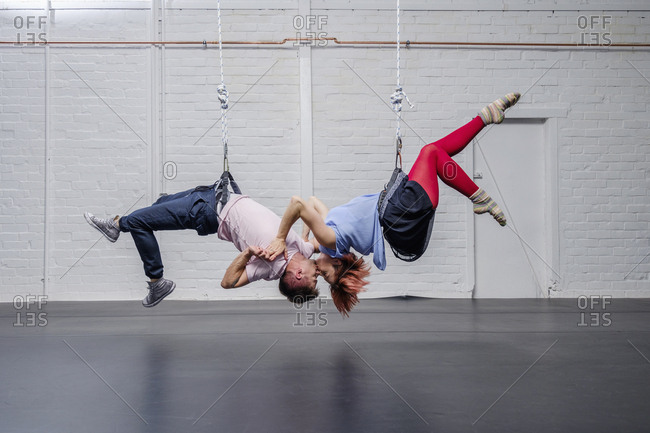 Modern aerialist dancers performing, hanging upside-down and kissing