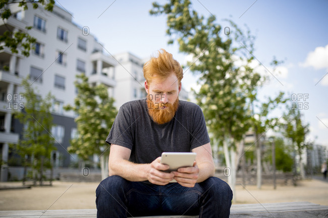 Man with beard using digital tablet on urban bench