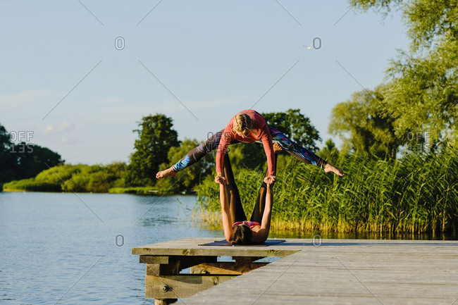 Women practicing acro yoga on sunny lakeside dock