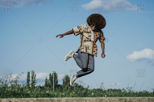Carefree young man with afro jumping for joy