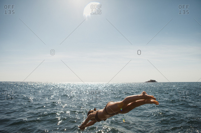 Woman diving into sunny blue ocean, Roving, Croatia