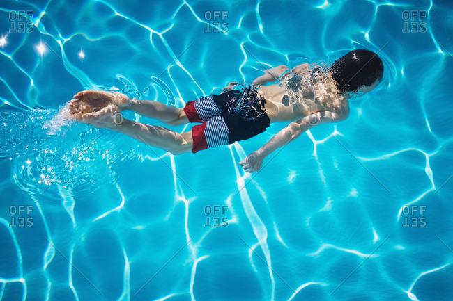 Boy swimming in blue swimming pool