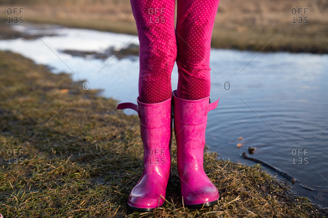 Girl stands in her rain boots