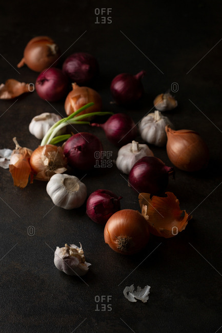 Onions and garlic on dark table