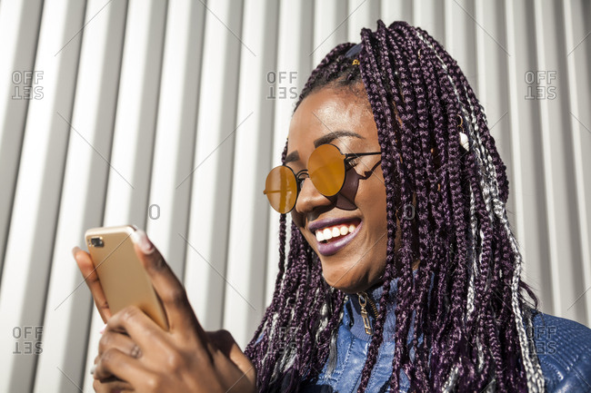 Beautiful, smiling and young afro woman with braids and sun glasses chatting with her smart phone