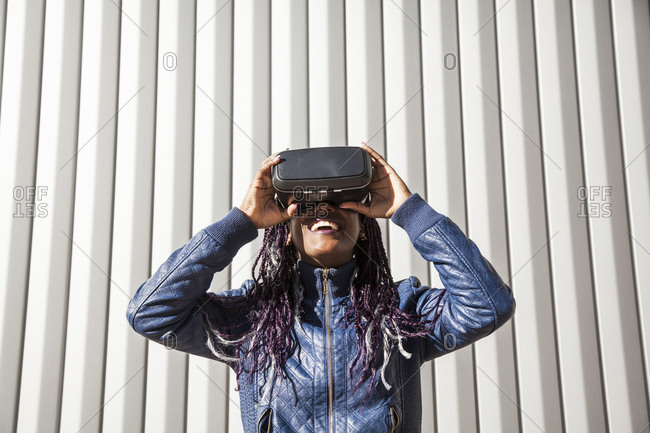 Beautiful, smiling and young afro woman with braids, playing video game with virtual reality glasses