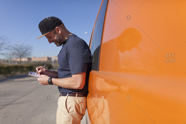 Urgent courier messenger checking his delivery tasks in his orange van