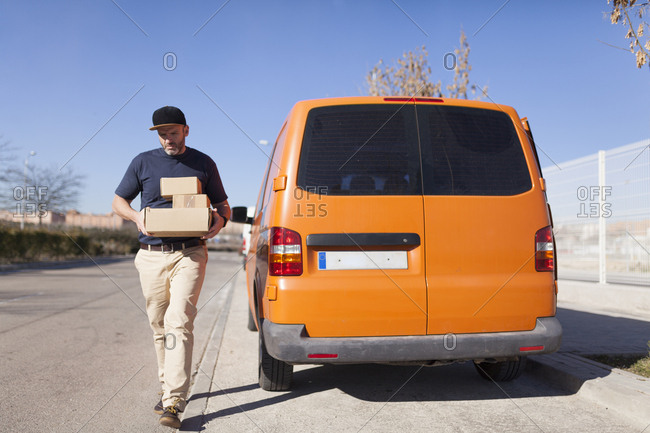 Urgent courier messenger in his orange van, getting off the vehicle with the delivery boxes
