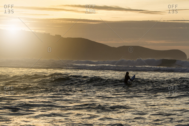 Beautiful young woman with her surfboard waiting for the wave in the light of sunset on a beach in northern Spain
