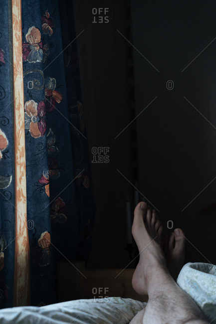 Crossed feet relaxing on a bed with closed curtains.