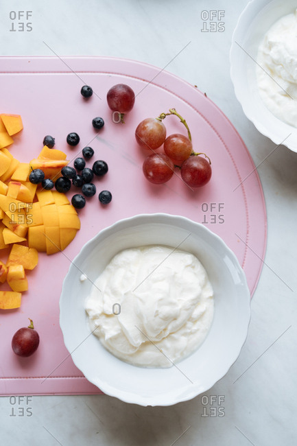 Bowl of yogurt near diced fruit on counter.