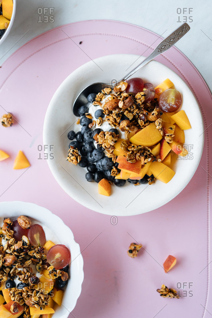 Yogurt, fruit and granola bowl with spoon in it on table.