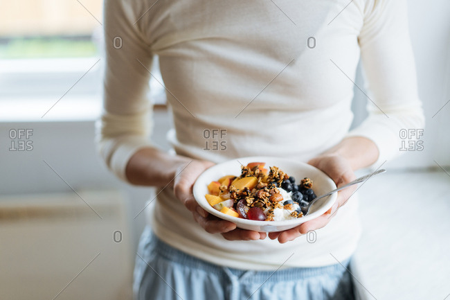 Woman holding bowl filled with yogurt, fruit and granola.