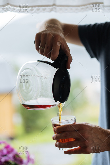 Man pouring coffee from a pot to a glass.