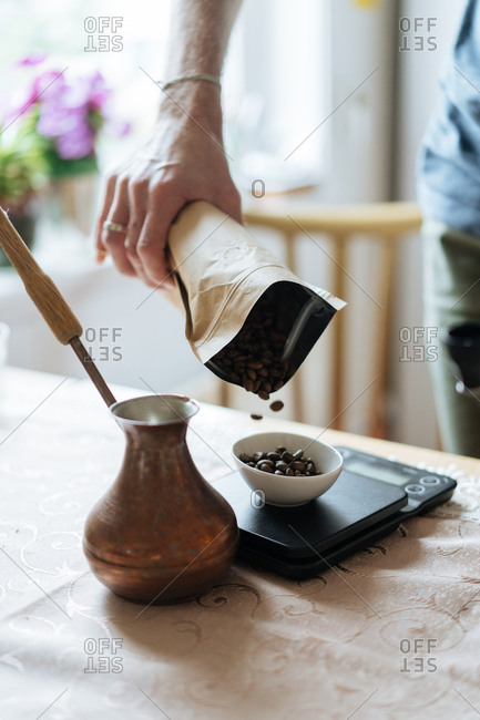 Pouring coffee beans on to scale to prepare before grinding.