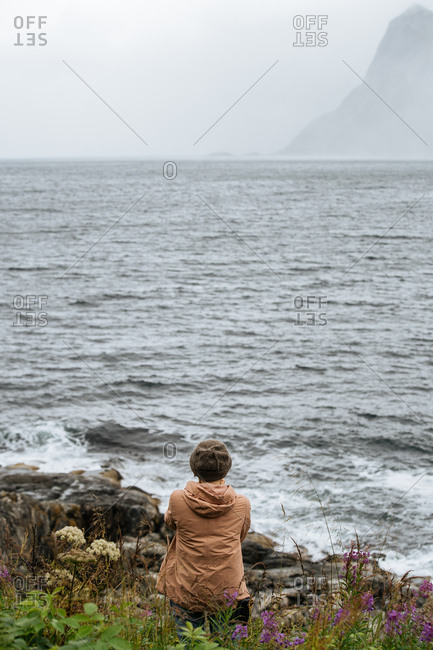Woman sitting on the shore near a big body of water.