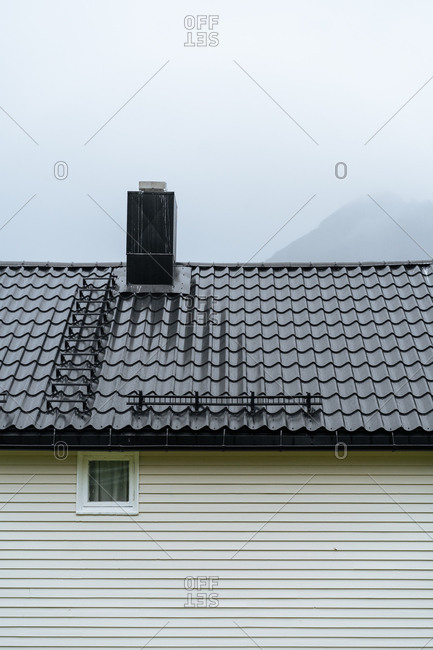 Close up of side of house and roof with sky in the background.