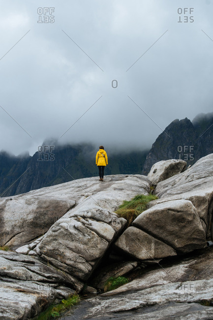 Woman stands on large rocks
