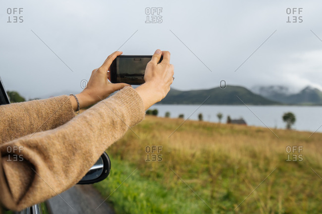 Woman taking photo out of car window